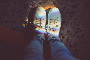 Perspective image of shoes with colorful rainbow highlights on dark background - POV picture