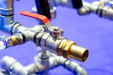 Close up of metal pipelines with ball valve.