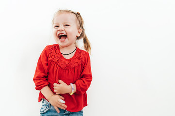 2a84265990 Cheerful laughing little girl in red blouse on the white background.