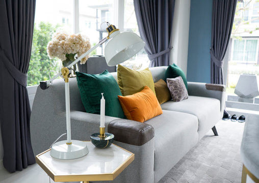White living room interior with yellow , blue and pink pillows on sofa. golden table lamp aside.