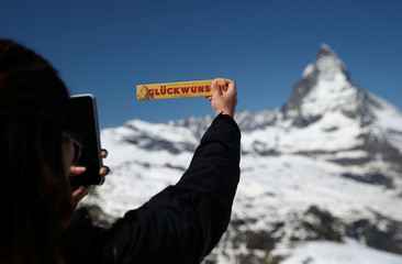 A tourist takes a picture of a Toblerone chocolate in front of the Matterhorn mountain at the Gornergrat in Zermatt