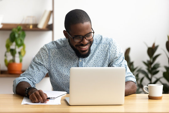 Head shot smiling african-american manager using laptop looking at screen