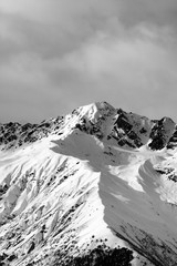 Fototapete - Black and white view on snow sunlit mountain and cloudy sky at winter evening