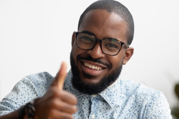 Portrait of smart smiling African American businessman gesturing thumbs up
