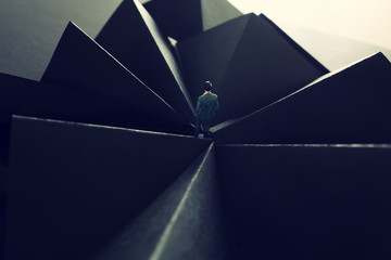 A picture of a miniature man stands in the geometric shapes looking forward .Concept of facing the unknown, taking a decision and finding solution.