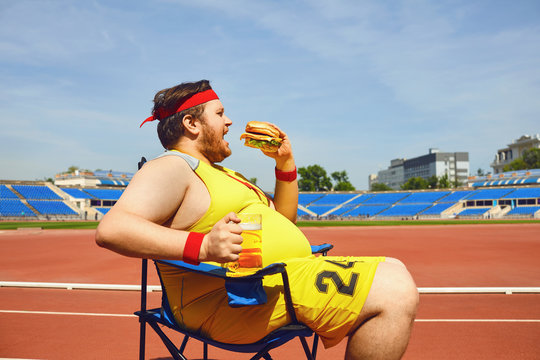 Fat man eating a burger and beer in training at the stadium.