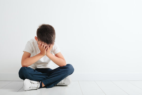 a child whose depression is sitting on the floor .