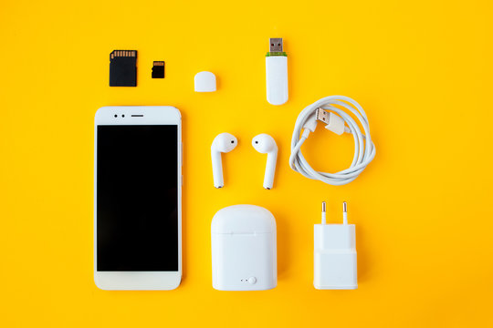 Mobile kit with smartphone, wireless headphones and chargers.