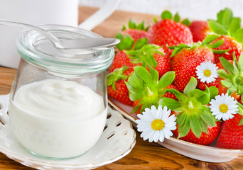 Strawberries and yogurt in a jar on wooden table