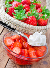 Fresh strawberries with cream on wooden table