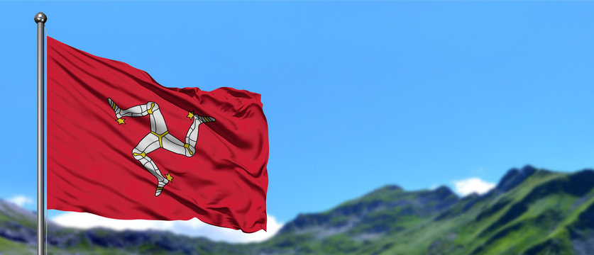 Isle Of Man flag waving in the blue sky with green fields at mountain peak background. Nature theme.