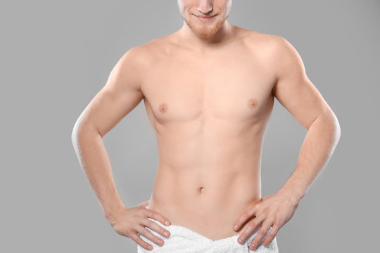 Young man with slim body in towel on grey background, closeup