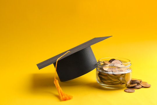 Glass jar, coins and graduation hat on color background. Space for text
