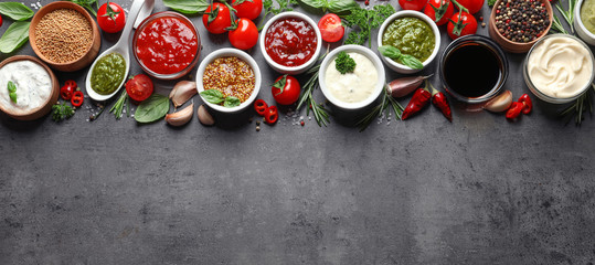 Flat lay composition with different sauces and space for text on gray background