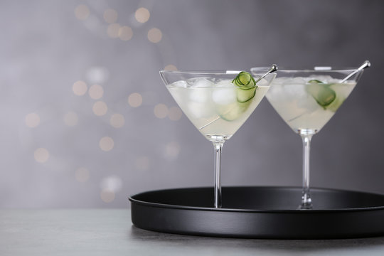 Glasses of martini with cucumber on tray against blurred lights. Space for text