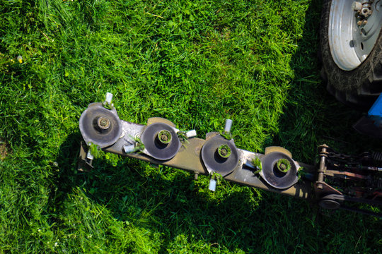 Mounted disc mower for  tractor during agricultural work, mows juicy green lawn grass during rapid rotation.