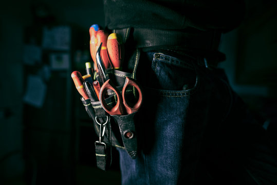 Detail of tools belt of electrician worker at home kitchen in low key screw, low key