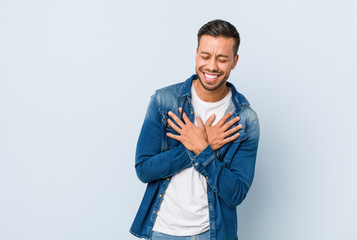 Young handsome filipino man laughing keeping hands on heart, concept of happiness.
