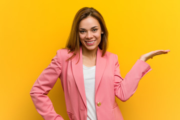 Young fashion business woman showing a copy space on a palm and holding another hand on waist. Wall mural