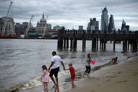 Families enjoy a beach along the Thames river with St. Paul's Cathedral visible in the background in London
