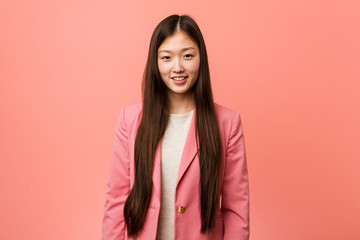 Young business chinese woman wearing pink suit happy, smiling and cheerful.