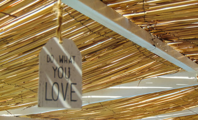 Do what you love inspirational quote hanging on the straw roof .