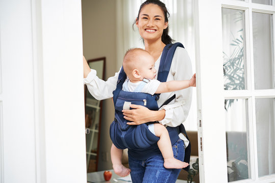 Happy young beautiful mixed-race woman carrying baby boy in sling when opening front door of her house