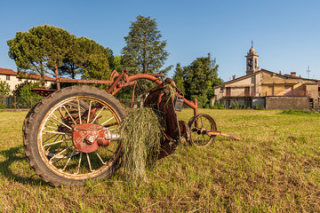 Summer landscape of a meadow with old red plow
