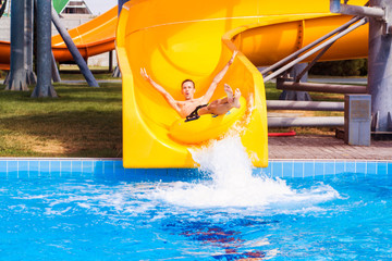 Funny excited man enjoying summer vacation in water park riding yellow float laughing.