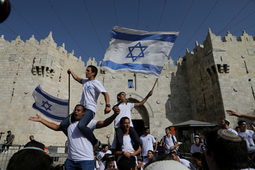 """Jewish youth wave Israeli flags as they participate in a march marking """"Jerusalem Day"""", near Damascus Gate in Jerusalem's Old City"""