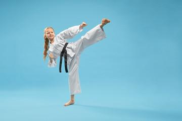 Karate girl in white kimono practicing martial arts.