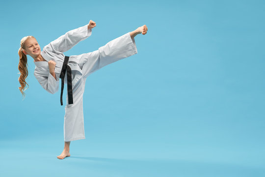 Positiive karate girl practicing kick foot forward.