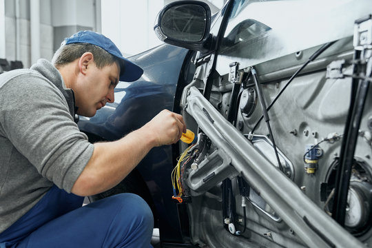 Side view of auto mechanic repairing electrical wires