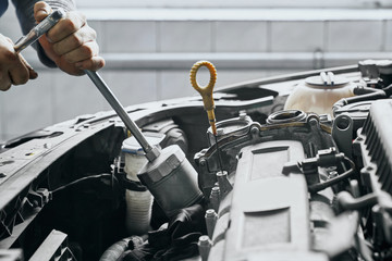 Close up of man's hands tighten piston cylinder by wrench
