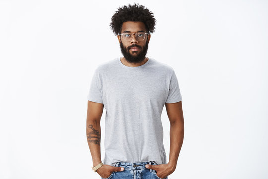 Portrait of calm and relaxed unemotional african american mature man with beard in glasses with pierced nose and tattoos holding hands in pockets looking at camera indifferent and unbothered