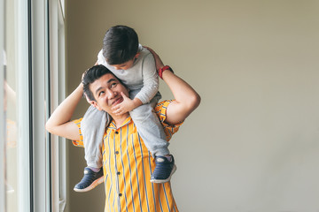 Cute son riding his father's throat standing by the window, Are happy to family concept.