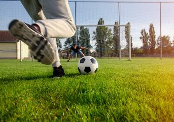 Closeup shot teen preparing to kick the ball , penalty shootout concept