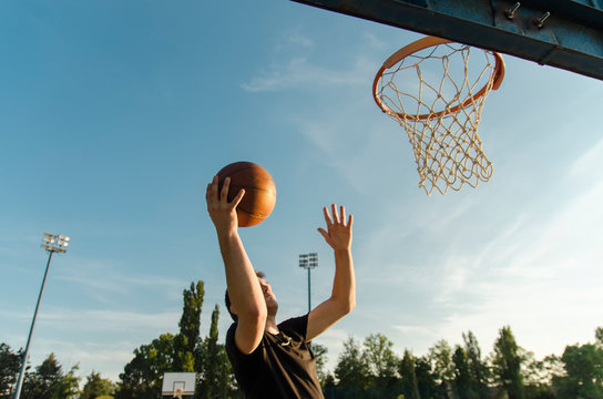 Teen jumping to score a point in basketball , layup shot