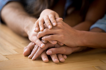 Close up of loving family stack hands showing unity
