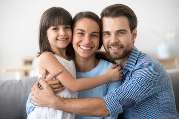 Portrait of happy family with kid hugging posing for picture
