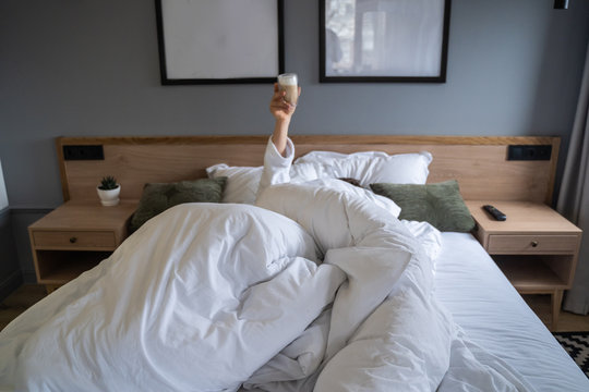 Hand holding a cup of coffee at home in bed