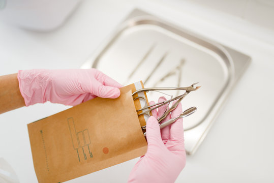 Cosmetologist in gloves holds manicure equipment
