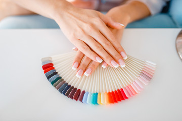 Poster de jardin Manicure Female hands and colorful nail varnish palette