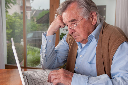 Frustrated senior man trying to use his modern laptop