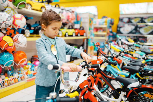 Little boy buying bicycle in kids store, side view