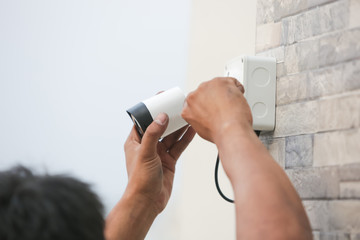 Technician installing CCTV camera for security service.