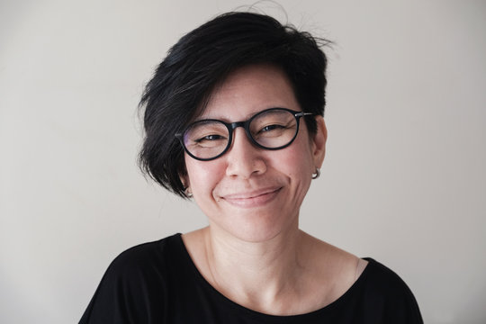 Portrait of happy and healthy natural looking middle aged Asian woman wearing glasses and smiling at camera