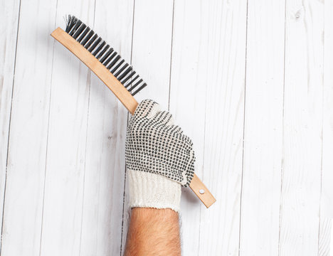 Tool. Hand in glove is holding wire metal brush on a white wooden background .
