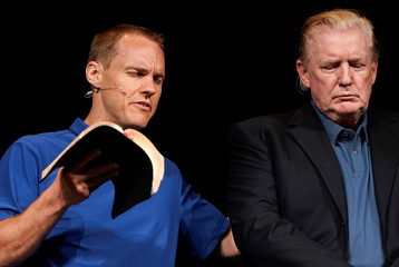 U.S. President Donald Trump stands on stage as Pastor David Platt prays for him at the McLean Bible Church, in Vienna