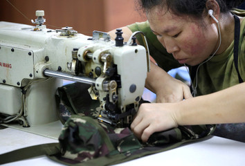 A worker sews on the production line of a factory of firearm equipment manufacturer Yakeda Tactical Gear Co, which exports most of its products to the United States, in Guangzhou